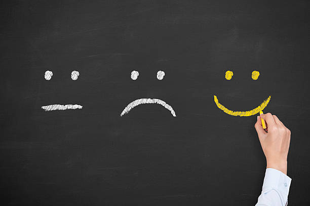 Unhappy and happy smileys on chalkboard - Photo