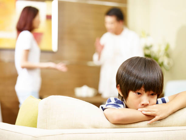 unhappy asian child and quarreling parents stock photo