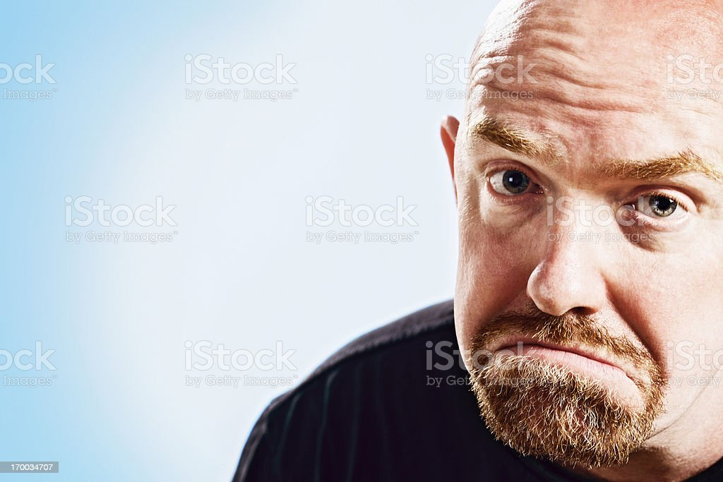 Unhappy, balding mature man frowns with furrowed brow stock photo