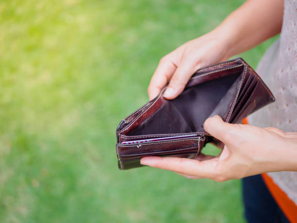 Unhappy bankrupt woman with empty wallet. Young woman shows her empty wallet. Bankruptcy Unhappy bankrupt woman with empty wallet. Young woman shows her empty wallet. Bankruptcy empty wallet stock pictures, royalty-free photos & images