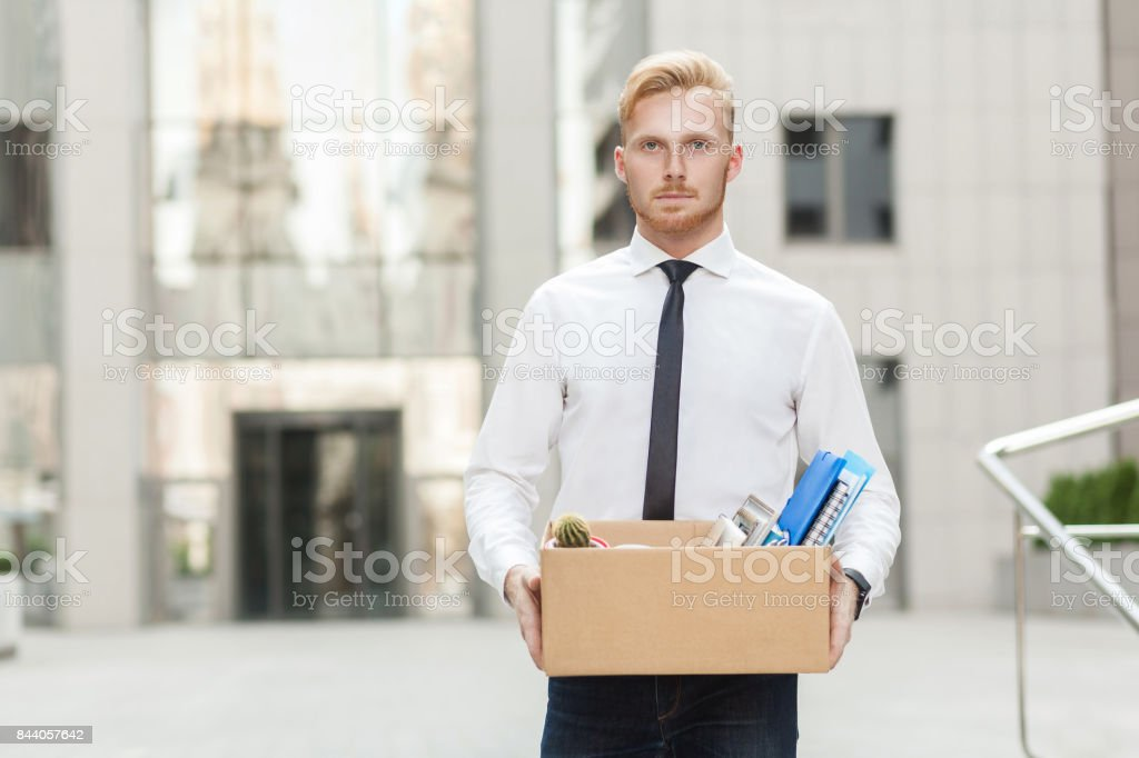 Unhappy bearded business man going out with cardboard, looking at camera and feeling looser. stock photo
