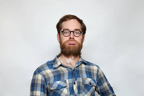 Unhappy bearded man in eyeglasses pouting his lips stock photo