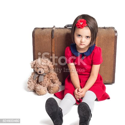 953553492 istock photo Unhappy beautiful little Girl with suitcase and toy bear 524900460