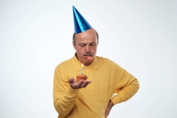 unglücklich geburtstag mann im gelben t-shirt und blaue kappe auf weißem hintergrund hält geburtstagstorte wünschen stehen. - geburtstag vergessen stock-fotos und bilder