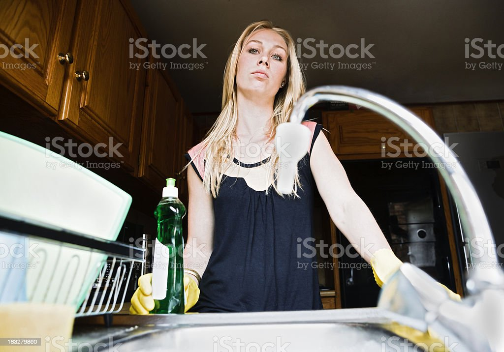 Unhappy blonde at kitchen sink. Dreaming of better days? royalty-free stock photo