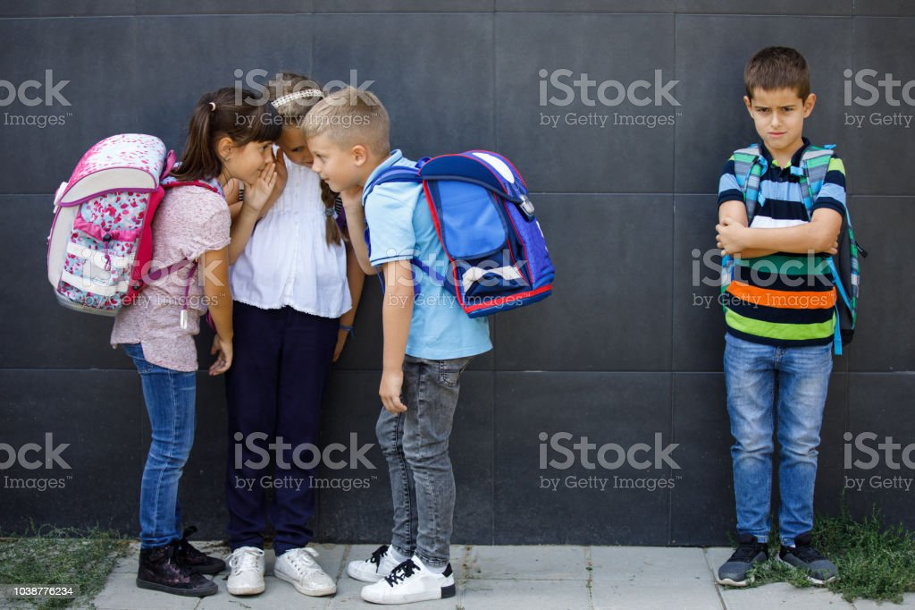 Unhappy boy being gossiped about by school friends stock photo