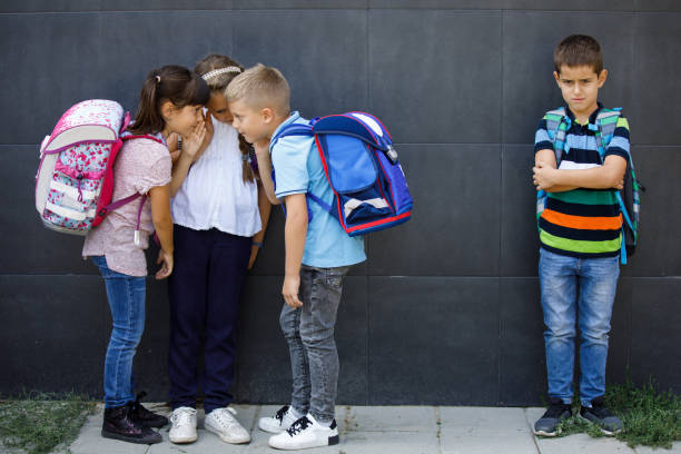 unhappy boy being gossiped about by school friends - disbarment stock pictures, royalty-free photos & images