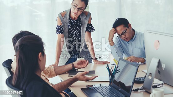 Unhappy business people in group meeting in office. The team is frustrated because of project failure. Business problem and crisis concept.