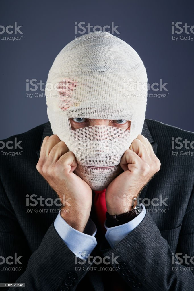 A businessman with his head covered in bloodstained dressings, rests...