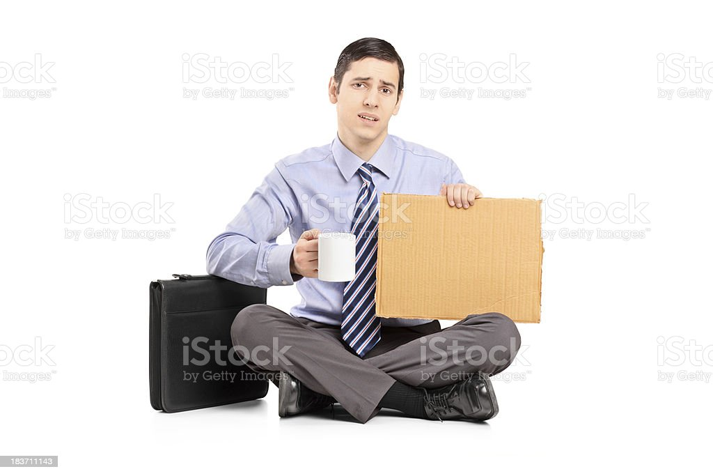 Unhappy businessman sitting on floor with cardboard royalty-free stock photo