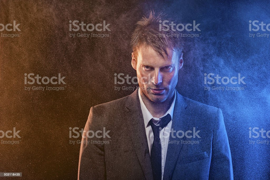 Unhappy businessman standing in the rain stock photo