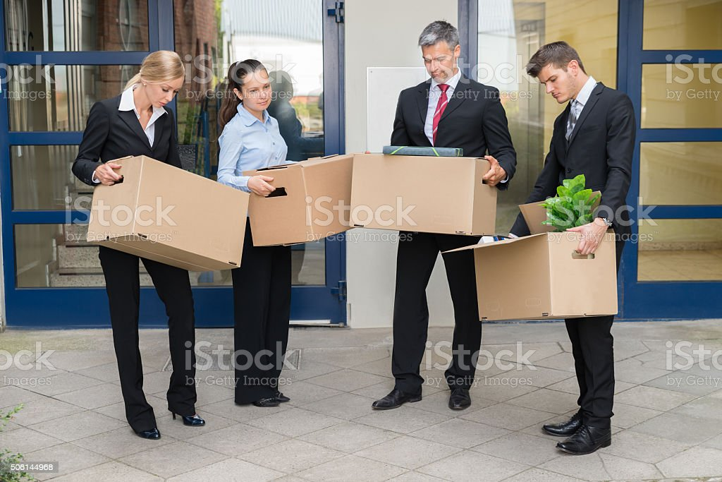 Unhappy Businesspeople With Cardboard Boxes Outside The Office stock photo
