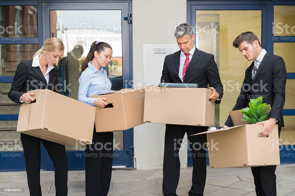 Unhappy Group Of Businesspeople Standing With Cardboard Boxes Outside...