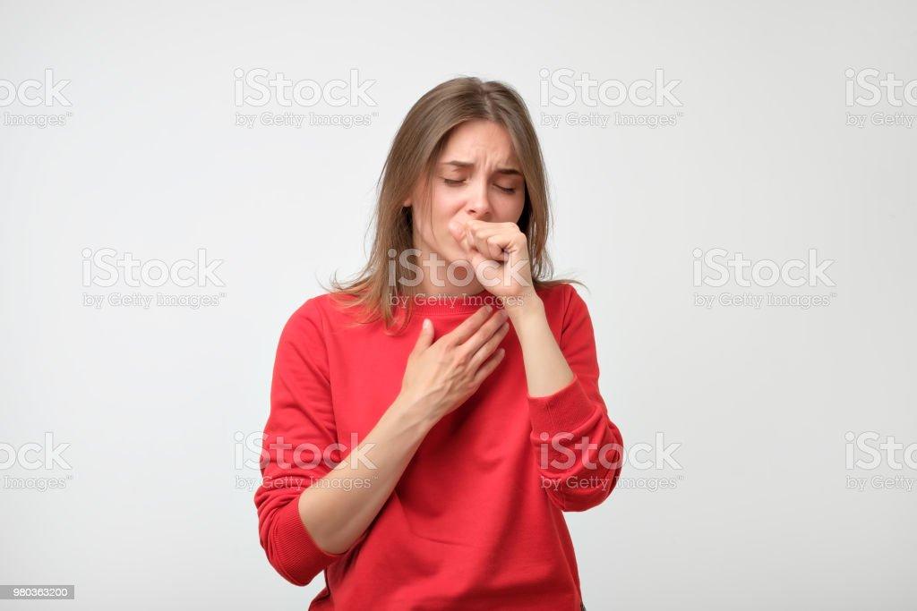 infeliz mujer caucásica en pulover rojo sufren de dolor de garganta al inicio - foto de stock