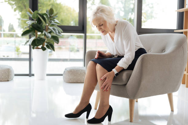 Unhappy cheerless woman looking at her legs Feeling tired. Unhappy cheerless aged woman sitting in the armchair and looking at her legs while feeling tired after a difficult working day leg stock pictures, royalty-free photos & images
