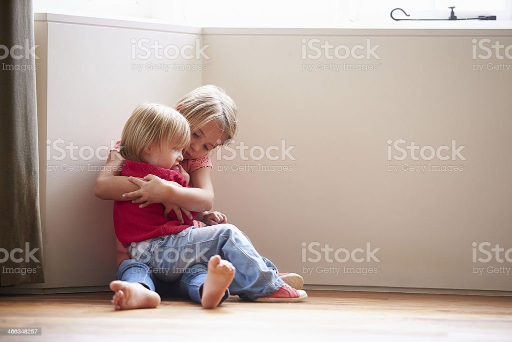 Unhappy Children Sitting On Floor In Corner At Home stock photo