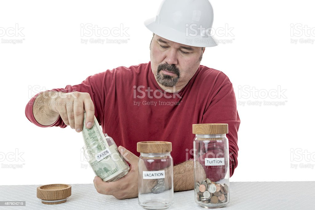 Unhappy construction worker paying the taxes stock photo