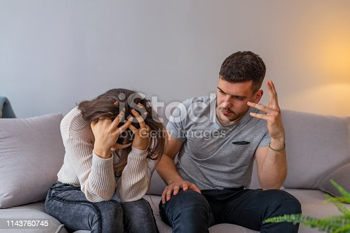 520496686istockphoto Unhappy couple having an argument in living room at home 1143760745
