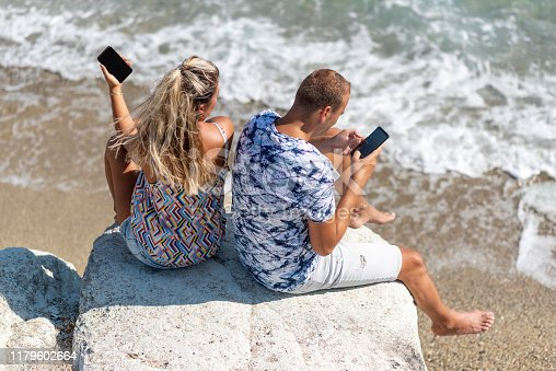 istock Unhappy couple ignoring each other using mobile phones 1179602664