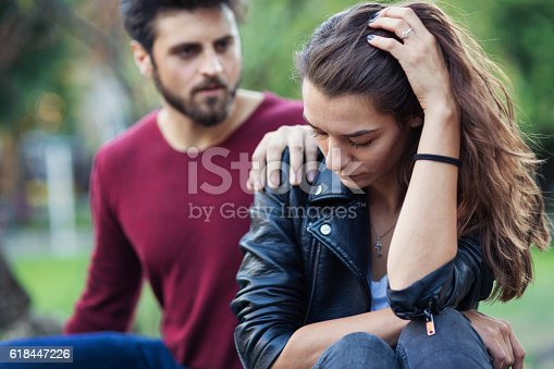 Unhappy looking couple sitting in the park and discussing and feeling gloomy