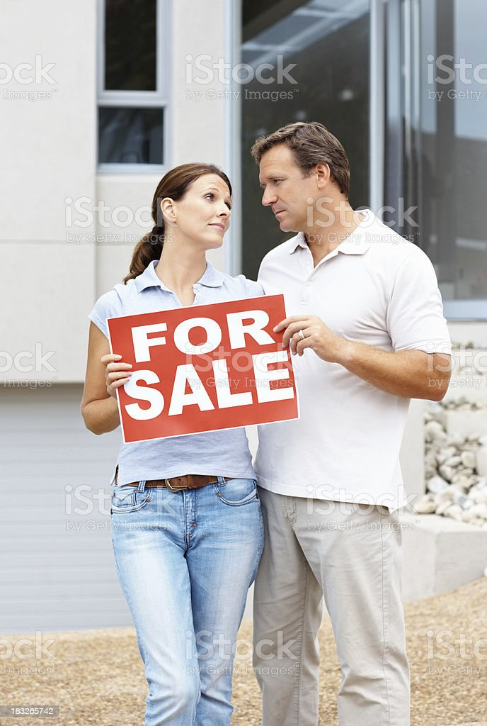 Unhappy couple putting house up for sale royalty-free stock photo