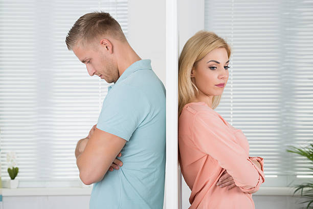 unhappy couple standing back to back at home - separation stock photos and pictures