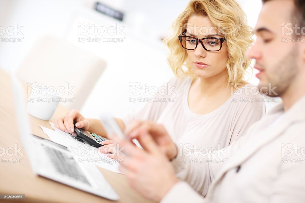Unhappy couple with documents at home stock photo