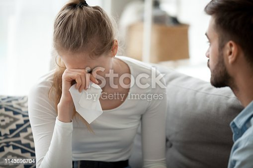 istock Unhappy couple, woman with handkerchief crying, relations problem 1143696704