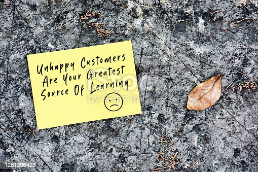 Unhappy customers are your greatest source of learning quote handwritten on a yellow paper on stone background in nature.