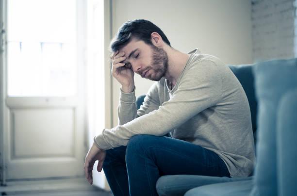 Unglücklich depressive kaukasische männliche sitzen und liegen dimeren Couch Gefühl verzweifelt ein einsameleiden an Depressionen. In gestresst von der Arbeit, Angst, Herz gebrochen und Männer Gesundheitskonzept. – Foto