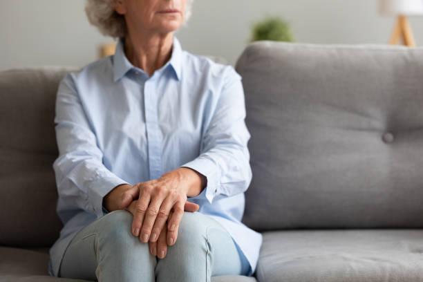 unhappy depressed senior woman sit alone on sofa, closeup view - solidão imagens e fotografias de stock