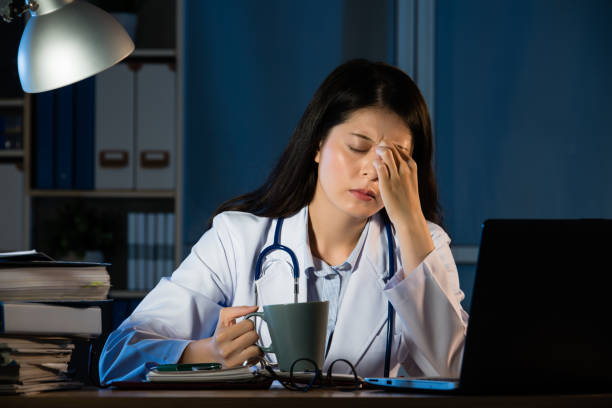 unhappy doctor with headache stressed holding coffee stock photo