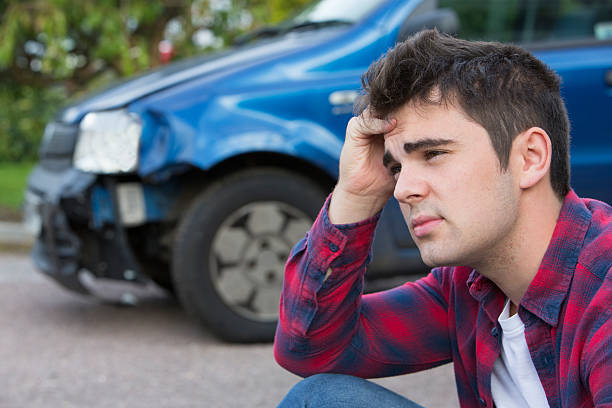 unhappy driver with damaged car after accident - impaired driving stock photos and pictures