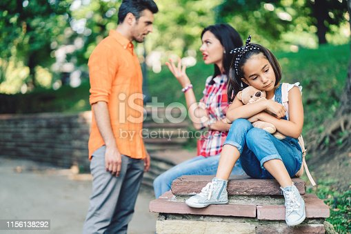 Young family arguing outside and sad daughter listening to them