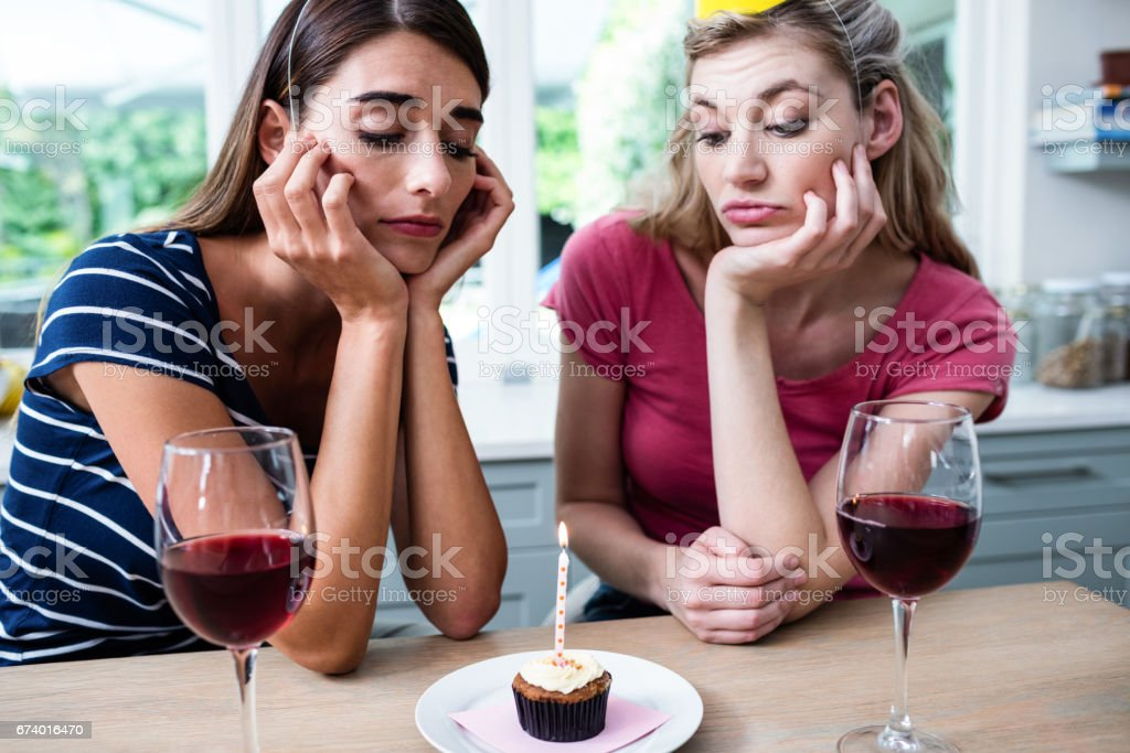 Unhappy friends sitting at table during birthday party stock photo