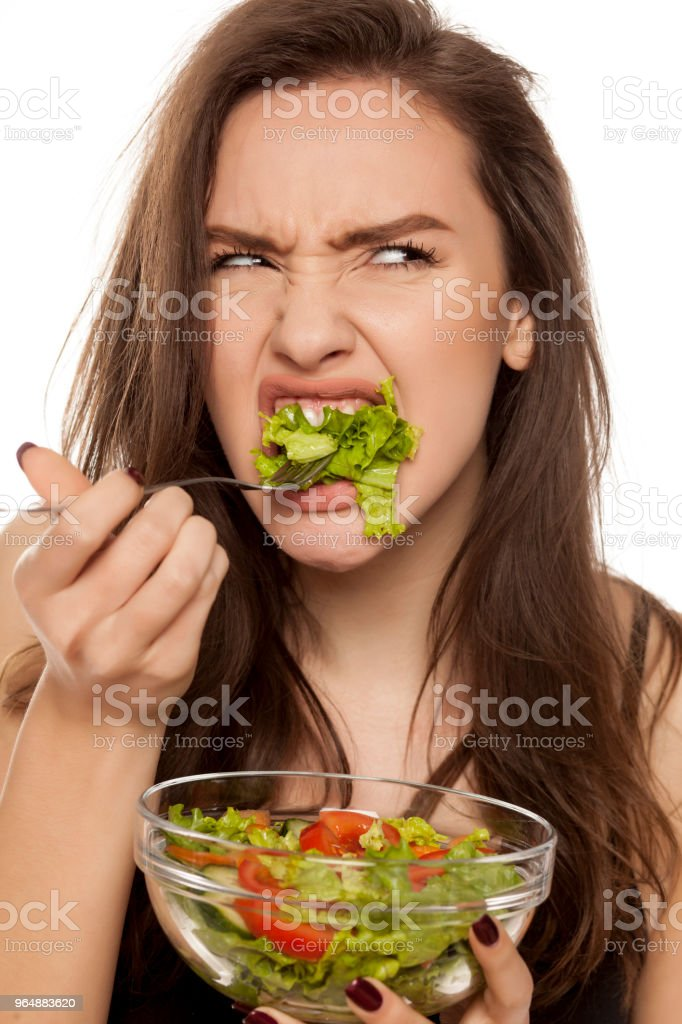 Unhappy frustrated young woman eat letuce salad on white background royalty-free stock photo