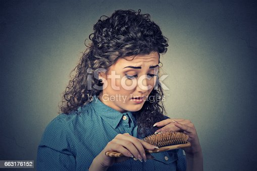 istock unhappy frustrated young woman surprised she is losing hair 663176152