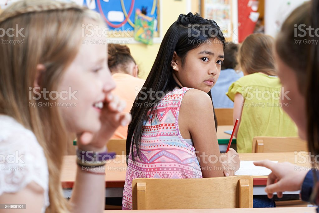 Unhappy Girl Being Gossiped About By School Friends In Classroom - foto de stock