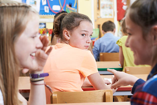 Unhappy Girl Being Gossiped About By School Friends In Classroom stock photo