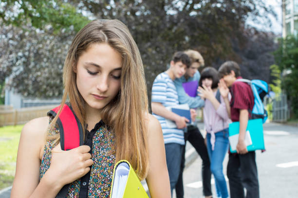 Unhappy Girl Being Gossiped About By School Friends stock photo