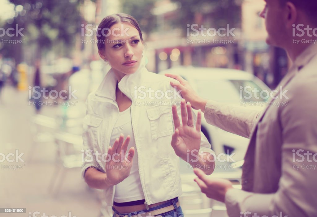 Unhappy girl getting rid of unwelcome stranger outdoors stock photo