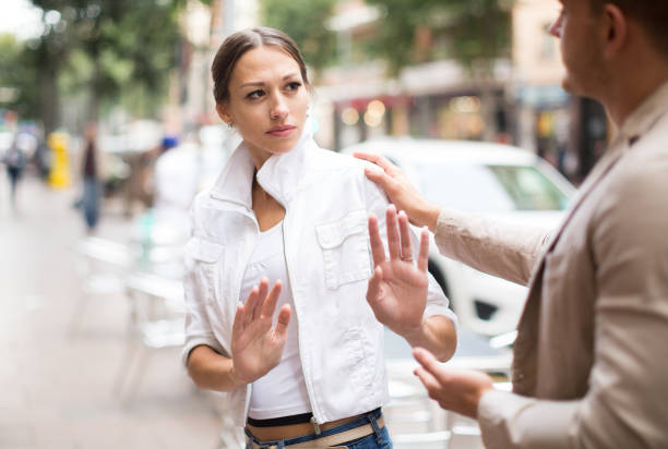 Unhappy girl getting rid of unwelcome stranger outdoors Portrait  of unhappy girl getting rid of unwelcome stranger outdoors harassment stock pictures, royalty-free photos & images