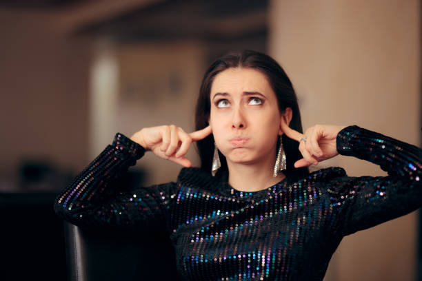 unhappy girl hating the loud bad music at a party - covering ears stock photos and pictures