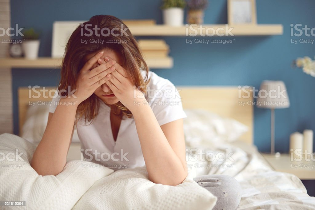 Unhappy girl in a bedroom stock photo