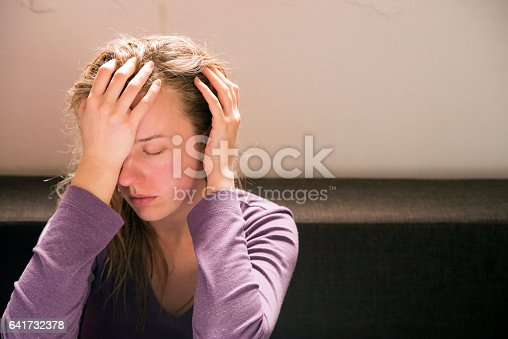 istock Unhappy girl in a bedroom 641732378