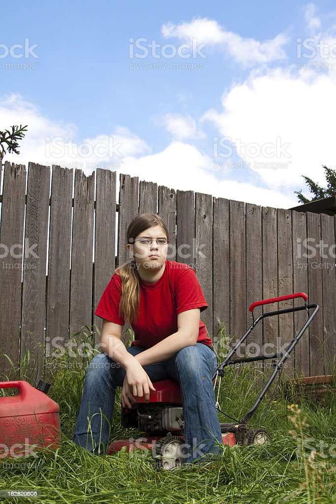 Unhappy Girl Mowing Lawn stock photo