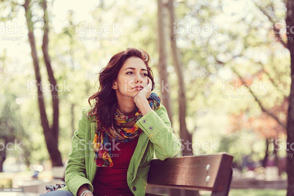 Unhappy girl sitting at bench ロイヤリティフリーストックフォト