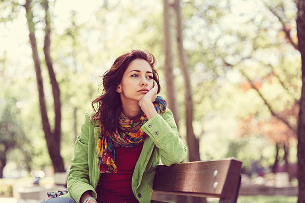 Unhappy girl sitting at bench stock photo