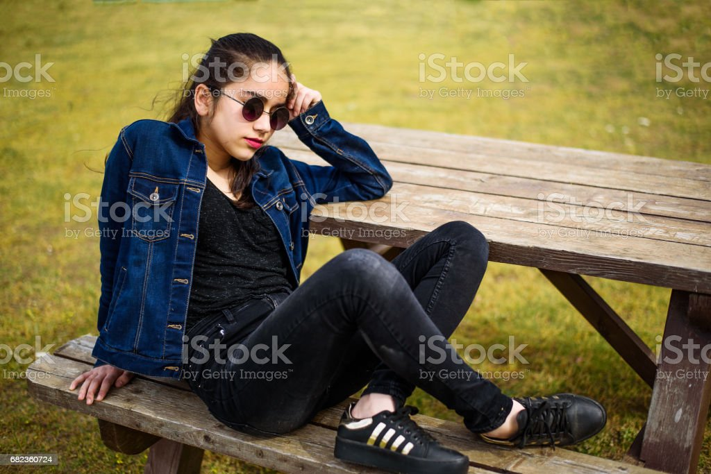 Unhappy girl sitting at picnic table foto stock royalty-free
