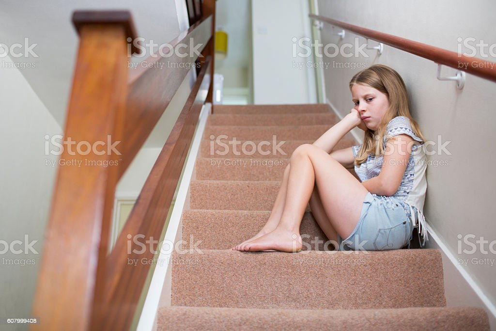 Unhappy Girl Sitting On Stairs At Home stock photo